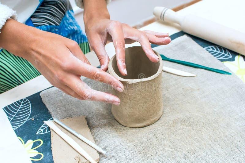 Junge Frau, die mit rohem Lehm an der Tonwarenwerkstatt arbeitet lizenzfreies stockbild