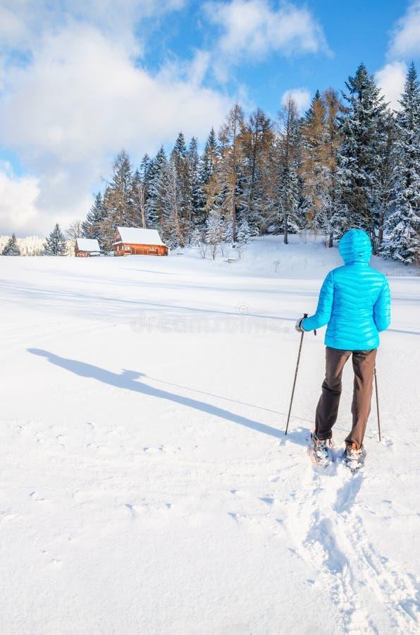 Junge Frau, die mit Schneeschuhen auf frischem Schnee geht stockbild