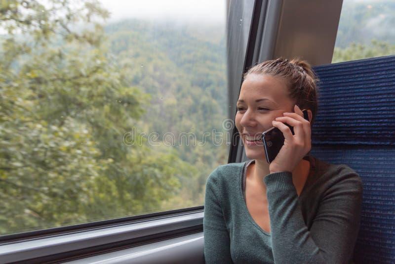 Junge Frau, die mit seinem Smartphone während einer Reise im Zug anruft, während sie arbeiten wird lizenzfreie stockfotos
