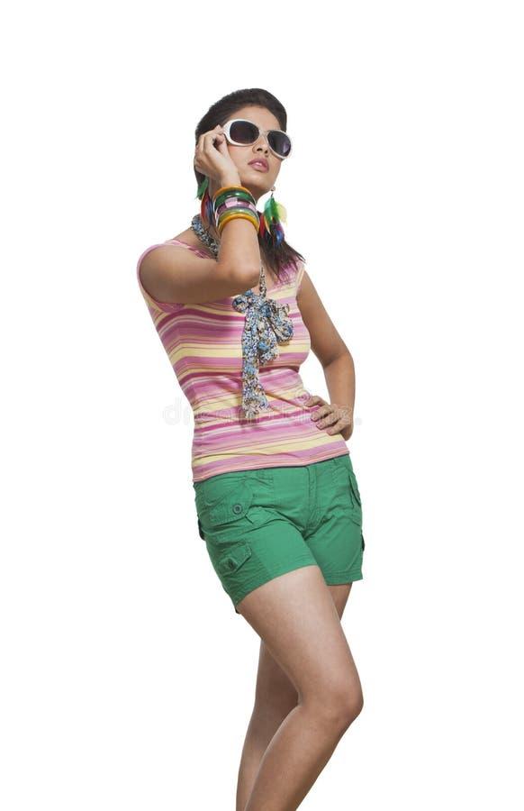 Junge Frau, die mit Sonnenbrille aufwirft stockbild