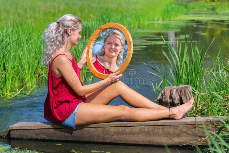 Junge Frau, die mit Spiegel am Rohwasser sitzt stockbild