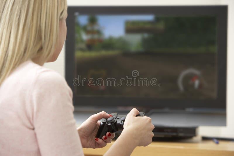 Junge Frau, die mit Spiel-Konsole spielt stockfoto