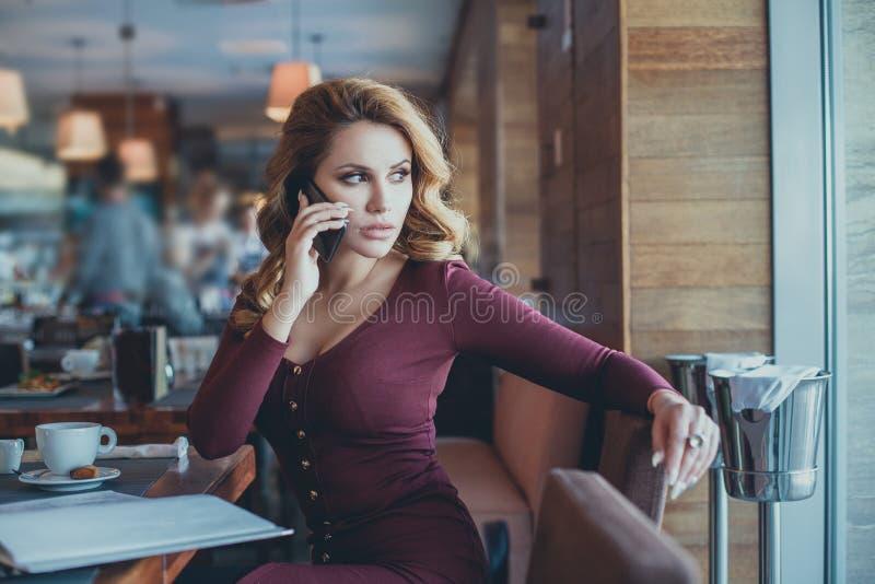 Junge Frau, die mit Zelltelefon beim allein sitzen nennt stockbilder