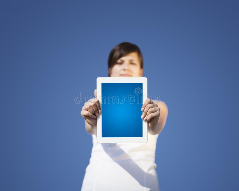 Junge Frau, die moderne Tablette betrachtet stockfotografie