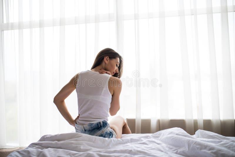 Junge Frau, die morgens auf dem Bett hat Rückenschmerzen sitzt lizenzfreie stockfotografie