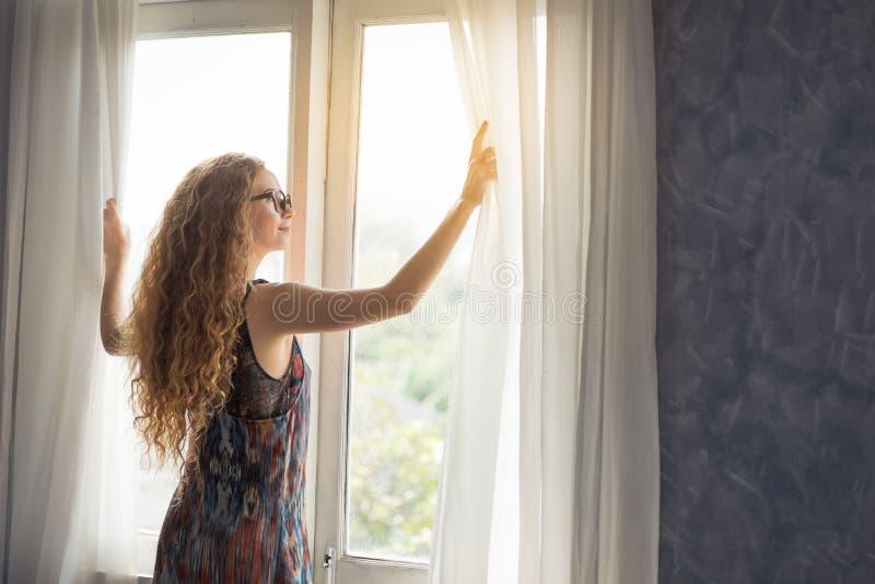 Junge Frau, die morgens den Vorhang öffnet stockbilder