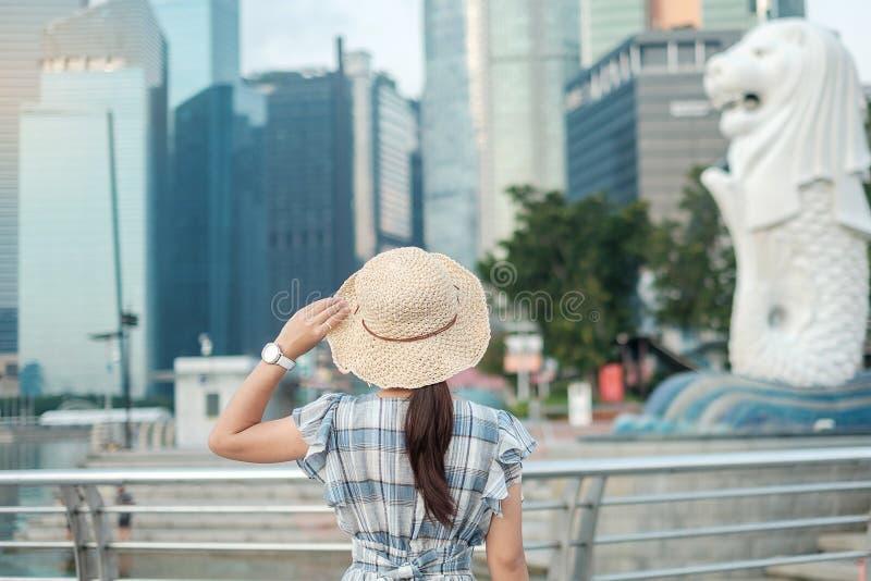 Junge Frau, die morgens mit Hut, glücklicher asiatischer Reisendbesuch im Singapur-Stadtstadtzentrum reist Markstein und popul?re lizenzfreies stockbild