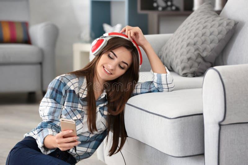 Junge Frau, die Musik durch Kopfhörer hört lizenzfreie stockfotografie
