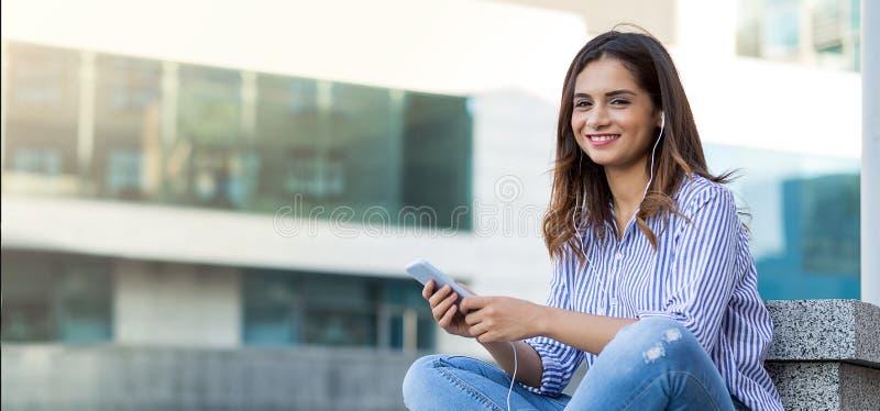 Junge Frau, die Musik hört und die Kamera im Freien mit Kopienraum betrachtet lizenzfreie stockfotografie