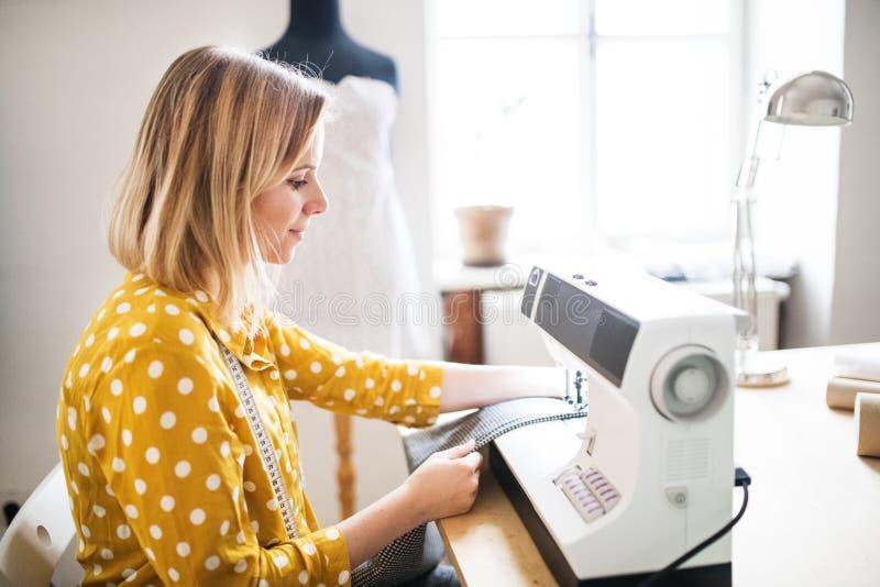 Junge Frau, die Nähmaschine, Startgeschäft verwendet lizenzfreies stockfoto