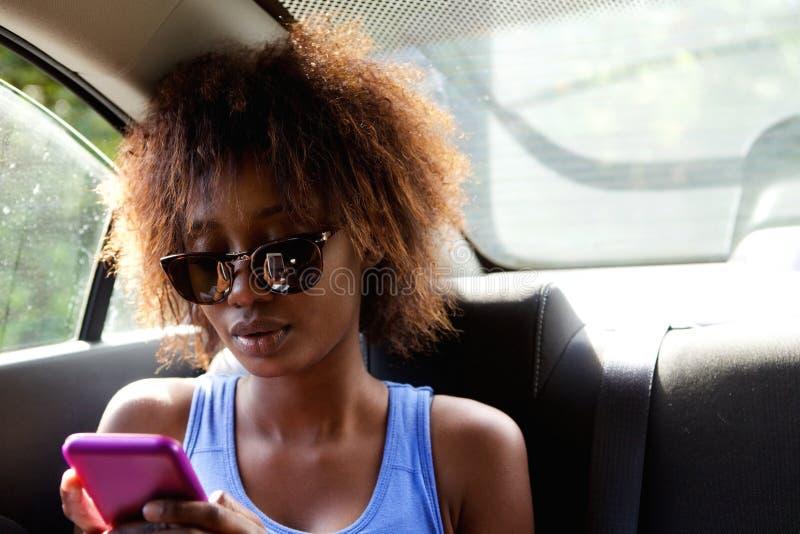 Junge Frau, die n-Rücksitz des Autos Handy betrachtend sitzt stockbild