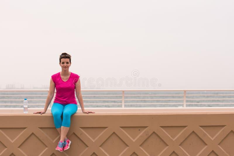 Junge Frau, die nach einem erfolgreichen Trainingslauf sitzt lizenzfreie stockfotografie