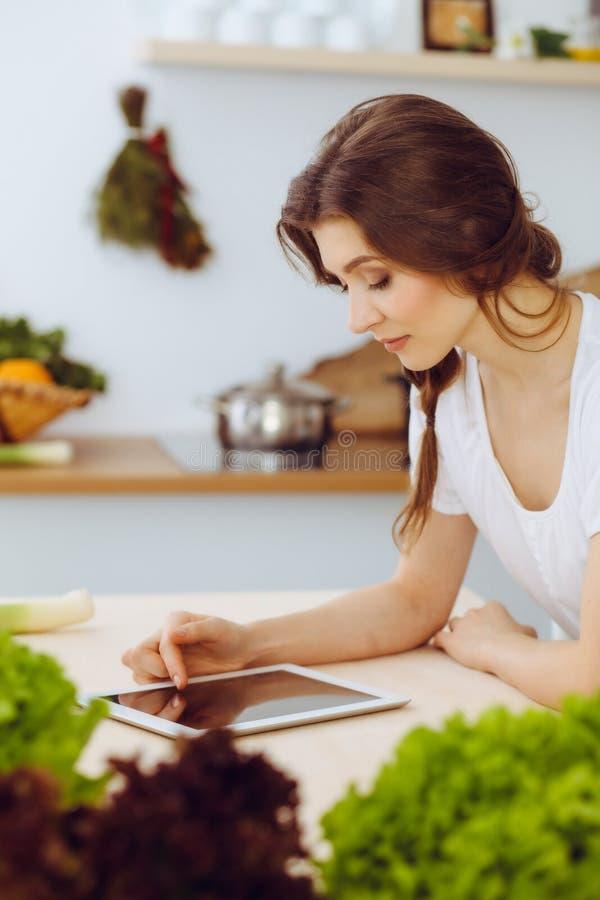 Junge Frau, die nach einem neuen Rezept f?r das Kochen in einer K?che sucht Hausfrau macht das on-line-Einkaufen durch Tablet-Com lizenzfreie stockbilder