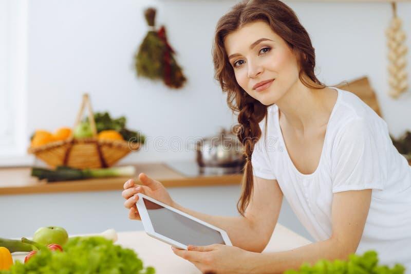 Junge Frau, die nach einem neuen Rezept f?r das Kochen in einer K?che sucht Hausfrau macht das on-line-Einkaufen durch Tablet-Com lizenzfreies stockbild