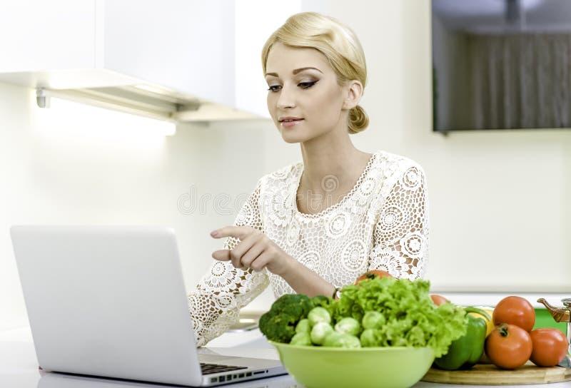 Junge Frau, die nach einem Rezept auf der Laptop-Computer in der Küche sucht stockfoto