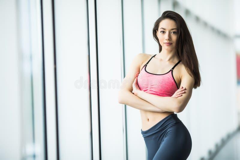 Junge Frau, die nach Training an der Turnhalle nahe Fenster stillsteht Eignungsfrau, die Pause nach Schulungseinheit im Fitnessst lizenzfreie stockbilder