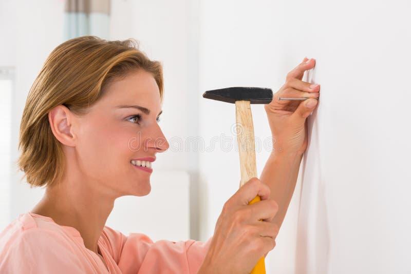 Junge Frau, die Nagel in einer Wand schlägt lizenzfreie stockbilder