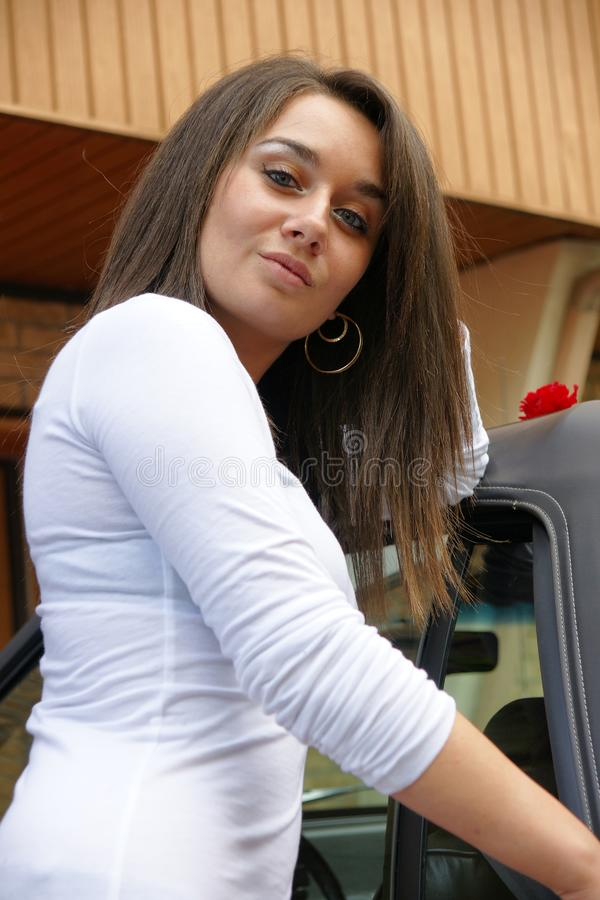 Junge Frau, die nahe bei einem Auto steht lizenzfreie stockfotografie