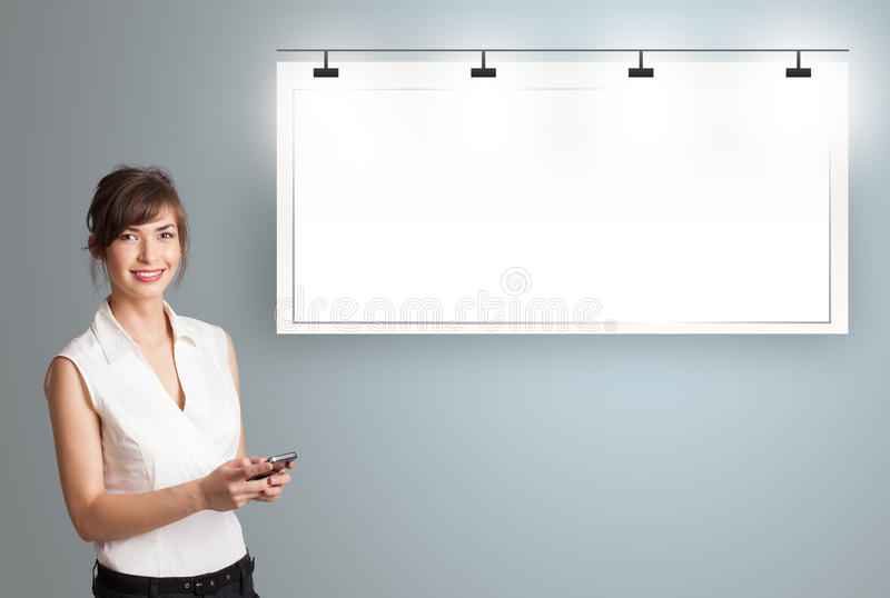 Junge Frau, die nahe bei einem modernen Kopienraum steht und ein p hält lizenzfreie stockbilder