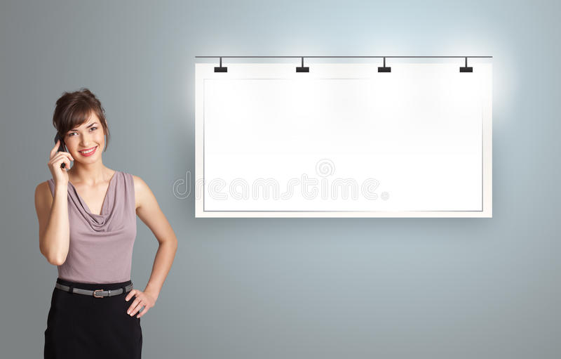Junge Frau, die nahe bei einem modernen Kopienraum steht und Phon macht stockbilder