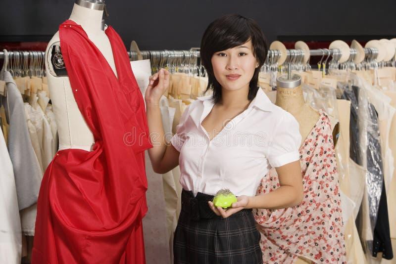 Junge Frau, die nahe dem Mannequin steht stockfoto