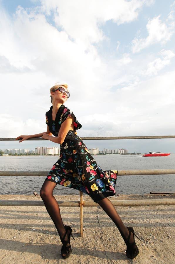 Junge Frau, die nahe dem Meer aufwirft. lizenzfreies stockfoto