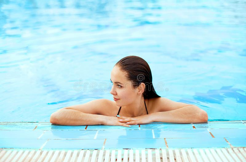 Junge Frau, die nahe dem Pool sitzt Sexy M?dchen mit gesunder gebr?unter Haut Frau mit dem Sonnenhut, der im Swimmingpool sich en stockbilder