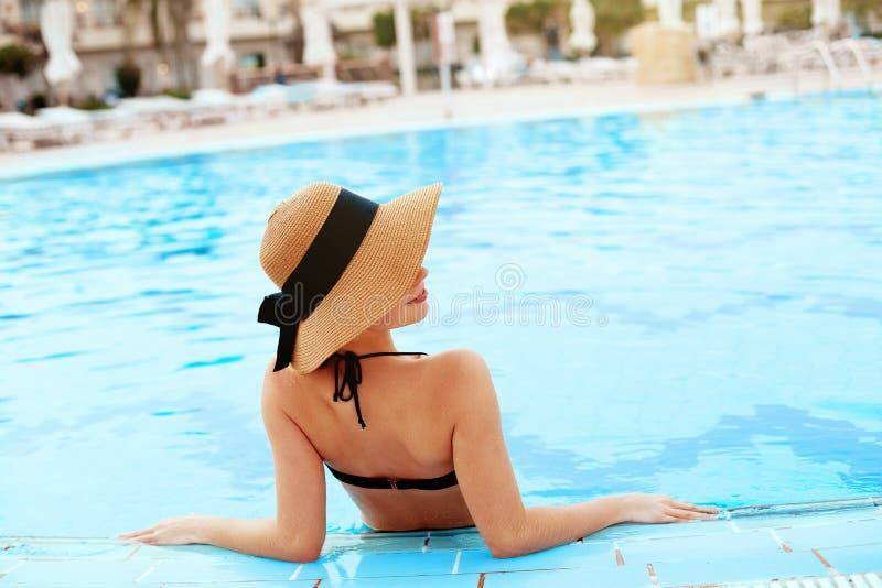 Junge Frau, die nahe dem Pool sitzt Sexy M?dchen mit gesunder gebr?unter Haut Frau mit dem Sonnenhut, der im Swimmingpool sich en lizenzfreies stockbild