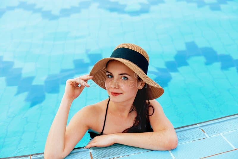 Junge Frau, die nahe dem Pool sitzt Sexy M?dchen mit gesunder gebr?unter Haut Frau mit dem Sonnenhut, der im Swimmingpool sich en lizenzfreie stockfotografie