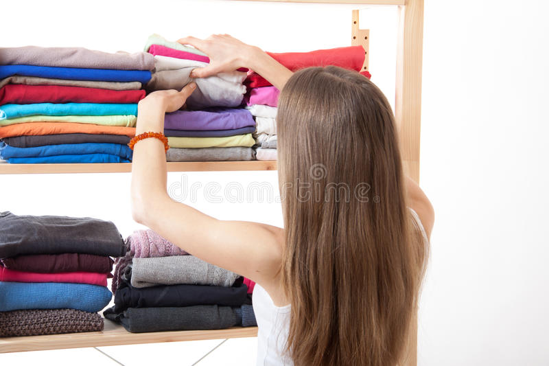 Junge Frau, die nahe der Garderobe steht stockbilder