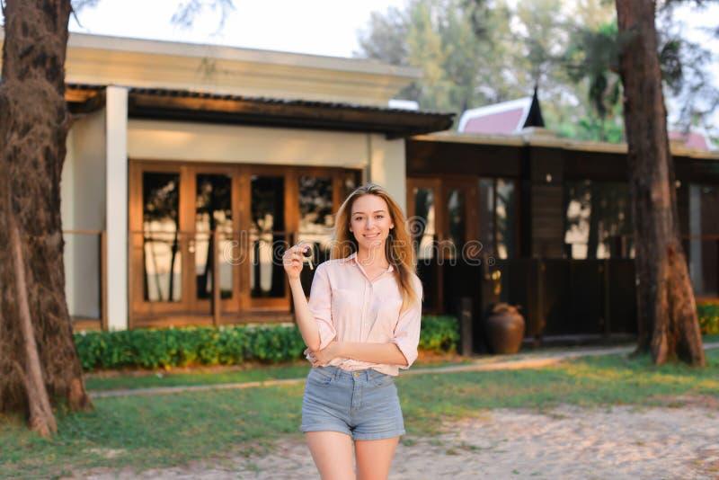Junge Frau, die nahes Erholungsorthaus steht und Schlüssel hält lizenzfreie stockfotografie