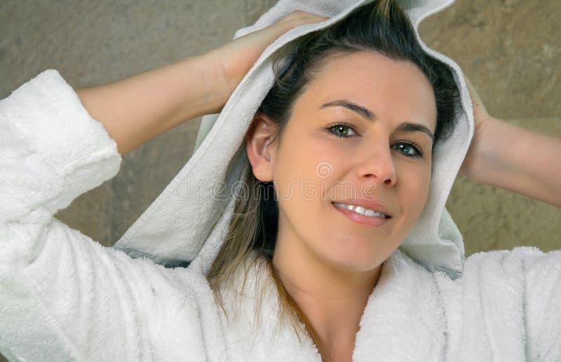 Junge Frau, die nasses Haar mit einem Tuch abwischt stockfotos