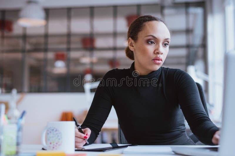 Junge Frau, die neue Geschäftsaufgabe bearbeitet stockfoto