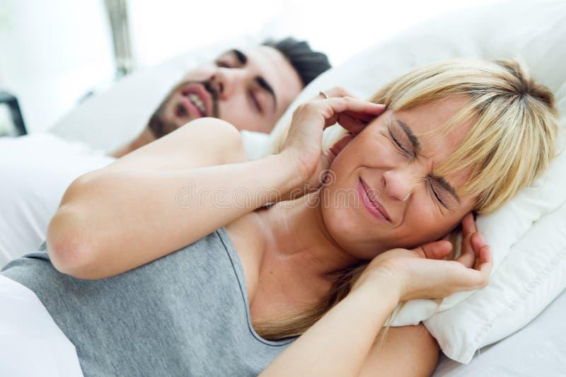 Junge Frau, die nicht schlafen kann, weil ihr Ehemann schnarcht stockfoto