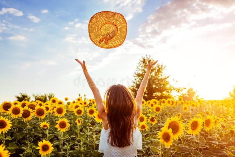 Junge Frau, die oben in blühenden werfenden Hut des Sonnenblumenfelds geht und Spaß hat Krasnodar Gegend, Katya stockbilder