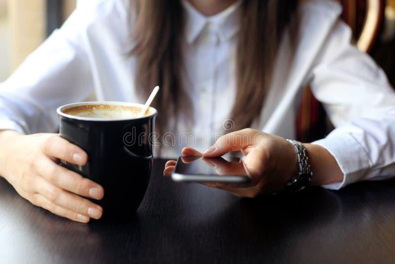 Junge Frau, die oben ihren Smartphoneabschluß grast stockbild