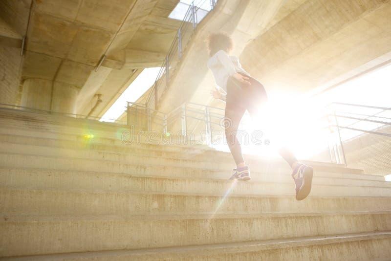 Junge Frau, die oben Treppe laufen lässt lizenzfreie stockbilder