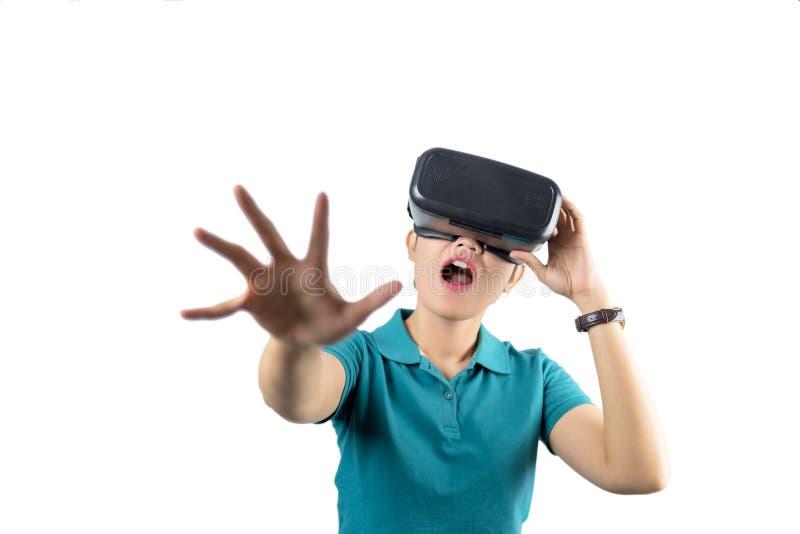 Junge Frau, die obwohl das VR-Gerät lokalisiert auf Weiß aufpasst stockbilder