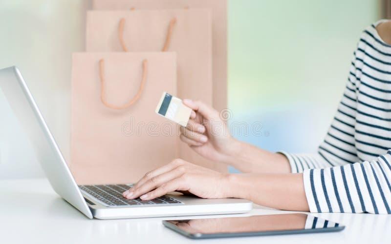 Junge Frau, die online mit Debet-/Kreditkarte-, Zahlungs- und Marketing-Konzept kauft stockbild