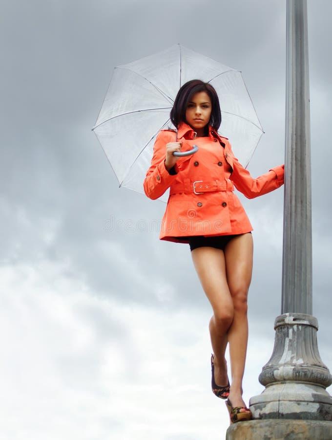 Junge Frau, die orange Grabenmantel trägt stockfotos