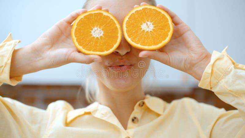 Junge Frau, die orange Scheiben nahe ihren Augen und Lächeln hält stockfoto