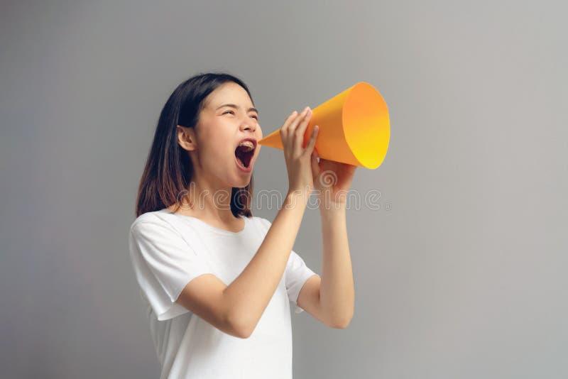 Junge Frau, die Papiermegaphon hält und in schreit stockfotografie
