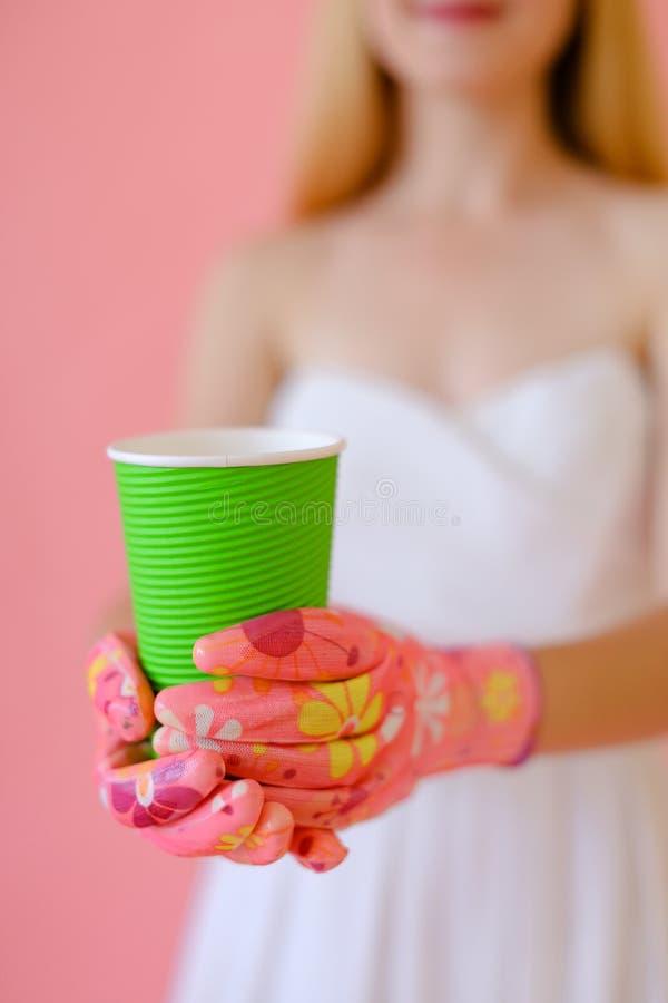 Junge Frau, die Papierschale hält und weißes Kleid, Fokus auf Glas trägt lizenzfreie stockbilder