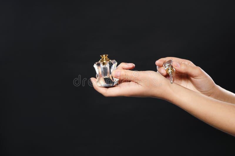 Junge Frau, die Parfüm auf Handgelenk gegen Schwarzes, Nahaufnahme anwendet lizenzfreies stockbild