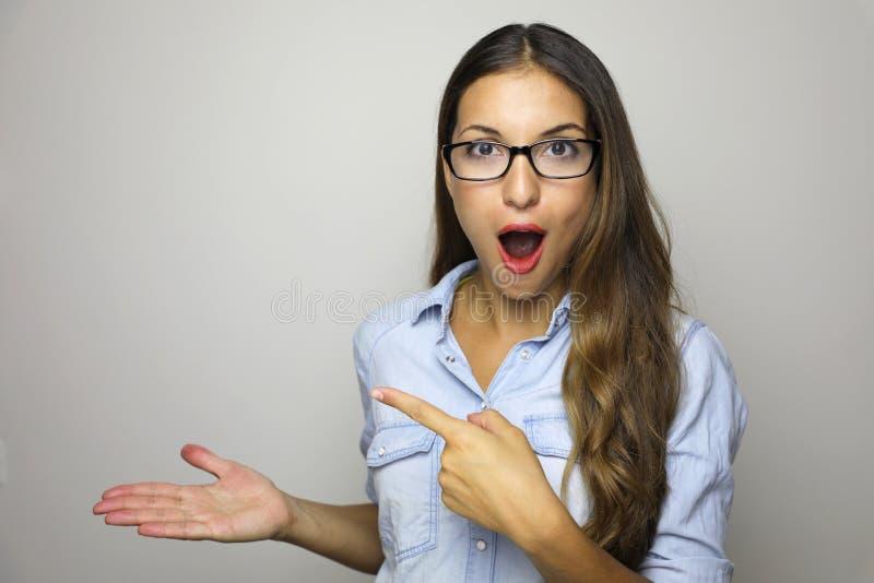 Junge Frau, die Produkt mit offener Handpalme zeigt und Finger zeigt Aufgeregter Ausdruck auf den tragenden Gläsern der Geschäfts lizenzfreie stockfotografie