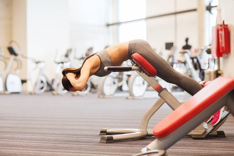 Junge Frau, die Rückenmuskulatur auf Bank in der Turnhalle biegt stockbild