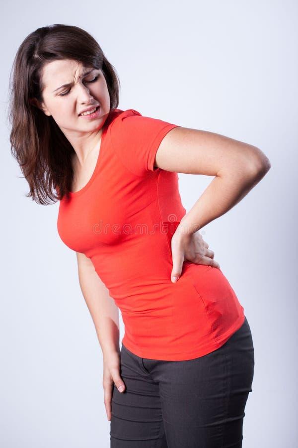 Junge Frau, die Rückenschmerzen hat stockfotos