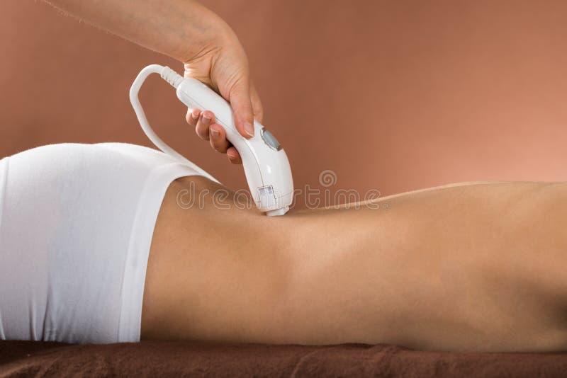 Junge Frau, die an Rückseite Laser-Therapie empfängt lizenzfreies stockfoto