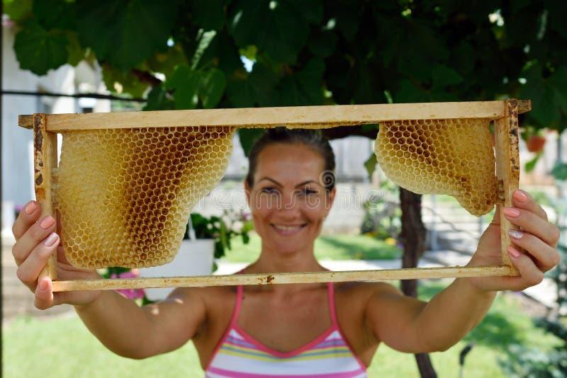 Junge Frau, die Rahmen mit Bienenwabe hält stockfoto