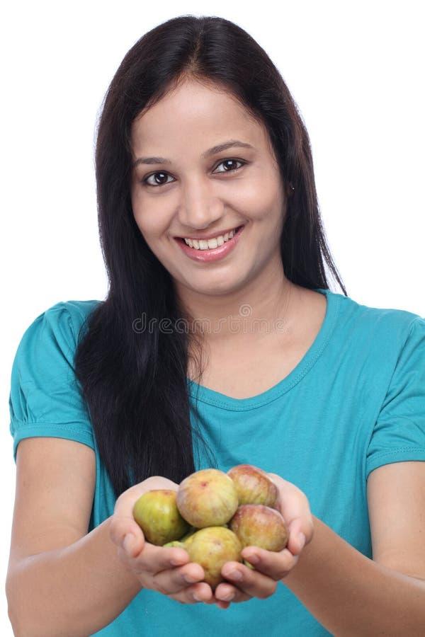 Junge Frau, die reife Feigen in ihren Händen hält lizenzfreies stockbild